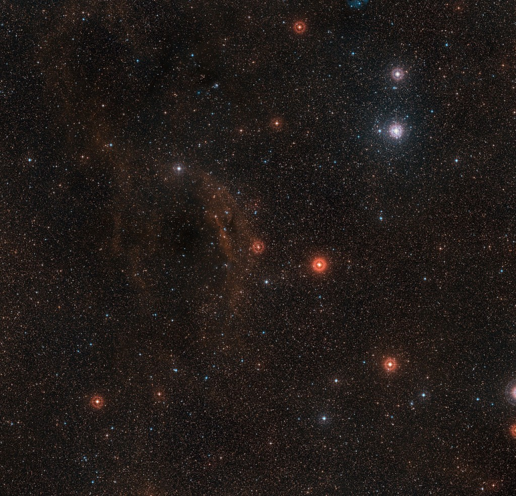 This wide-field view shows the sky around the very brilliant red hypergiant star VY Canis Majoris, one of the largest stars known in the Milky Way. The star itself appears at the centre of the picture, which also includes clouds of glowing red hydrogen gas, dust clouds and the bright star cluster around the bright star Tau Canis Majoris towards the upper right. This picture was created from images forming part of the Digitized Sky Survey 2.